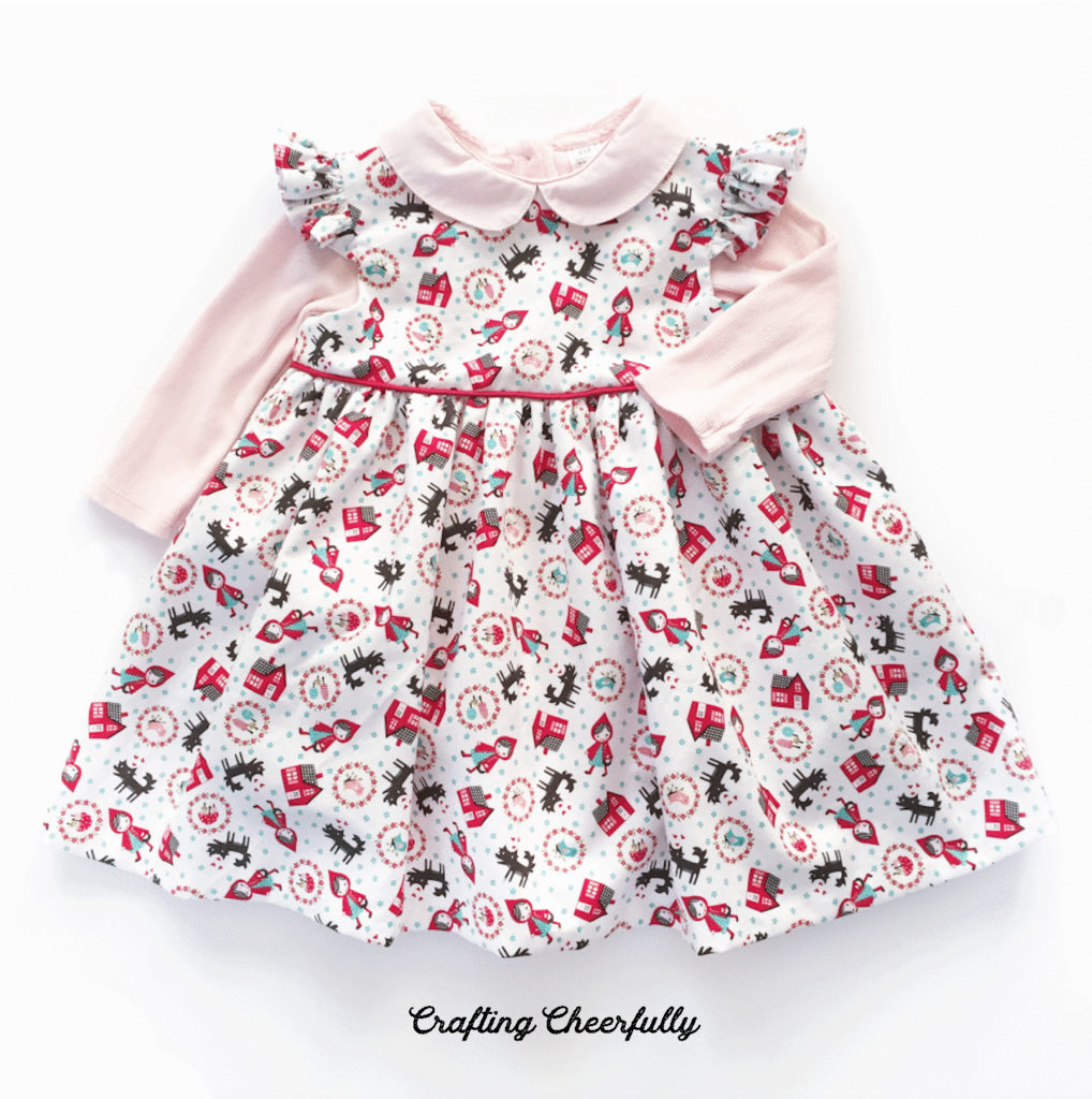 Little Red Riding Hood baby dress with pink onesie.
