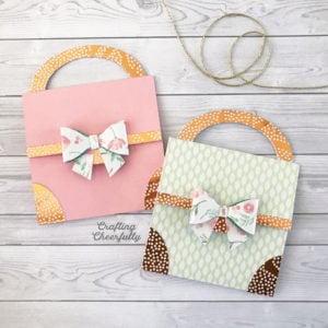Two pastel paper purse cards on a wooden background.