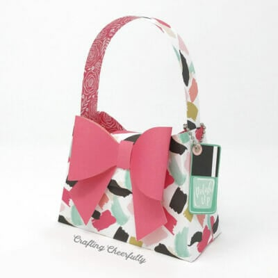 Paper purse with giant pink paper bow on the front with a small tag attached that looks like a bottle of nail polish.