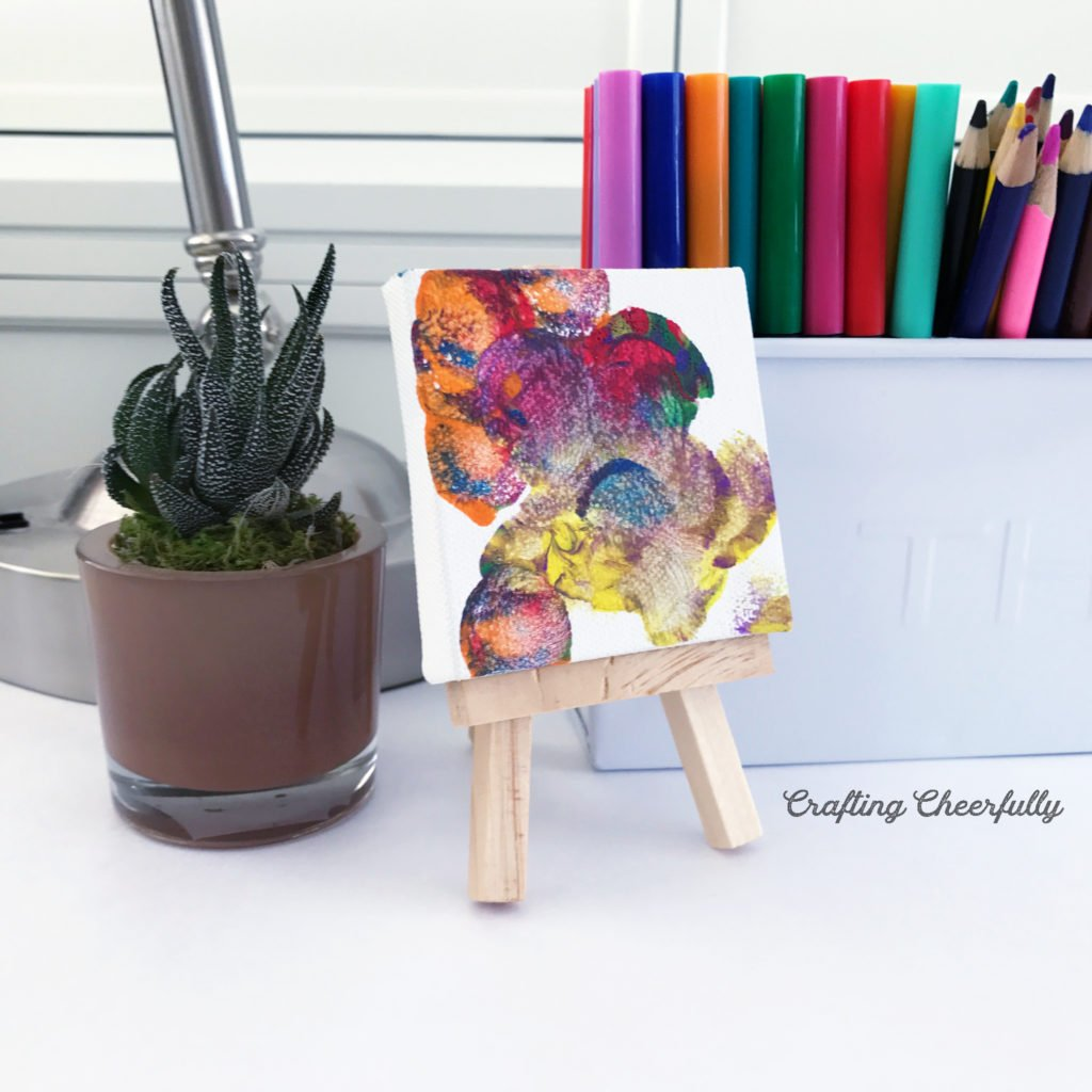 A mini canvas leaning up against a mini email is painted with bright colors sitting on a desk with colored pencils and a succulent..