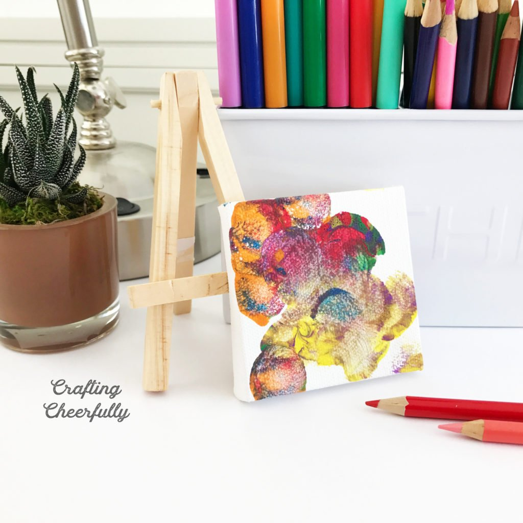 A mini canvas leaning up against a mini email is painted with bright colors sitting on a desk with colored pencils and a cactus.