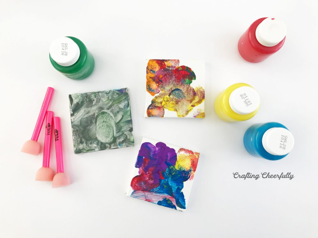 Three mini canvases lay on a tabletop with small pounce sponges and four containers of fingerpaint.
