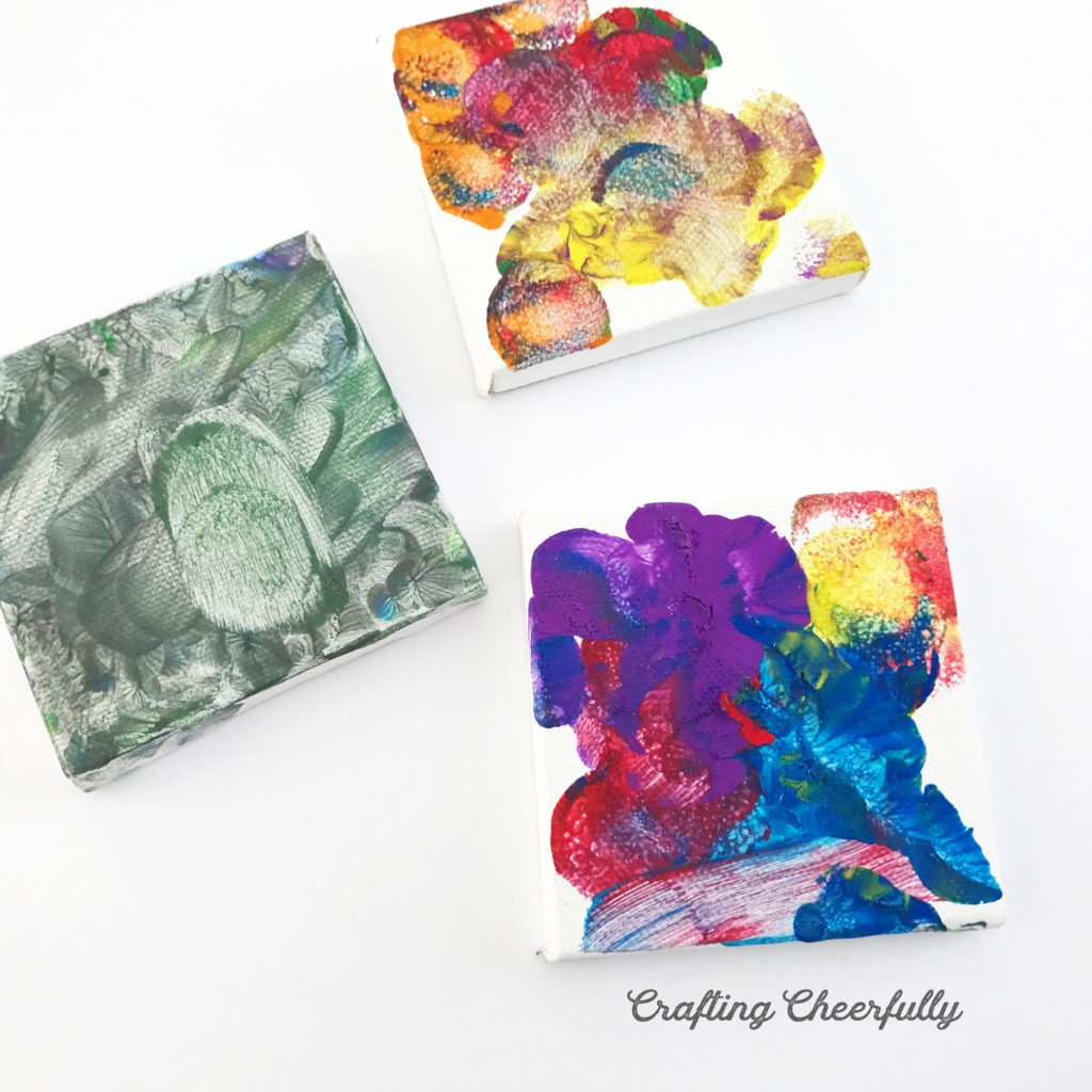 Three colorfully painted canvases on a white surface.