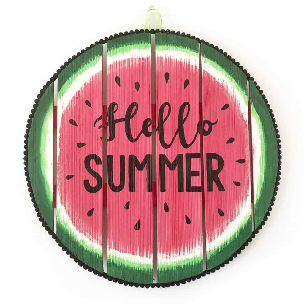 """Circular watermelon wooden sign with the words """"Hello Summer"""" on it."""