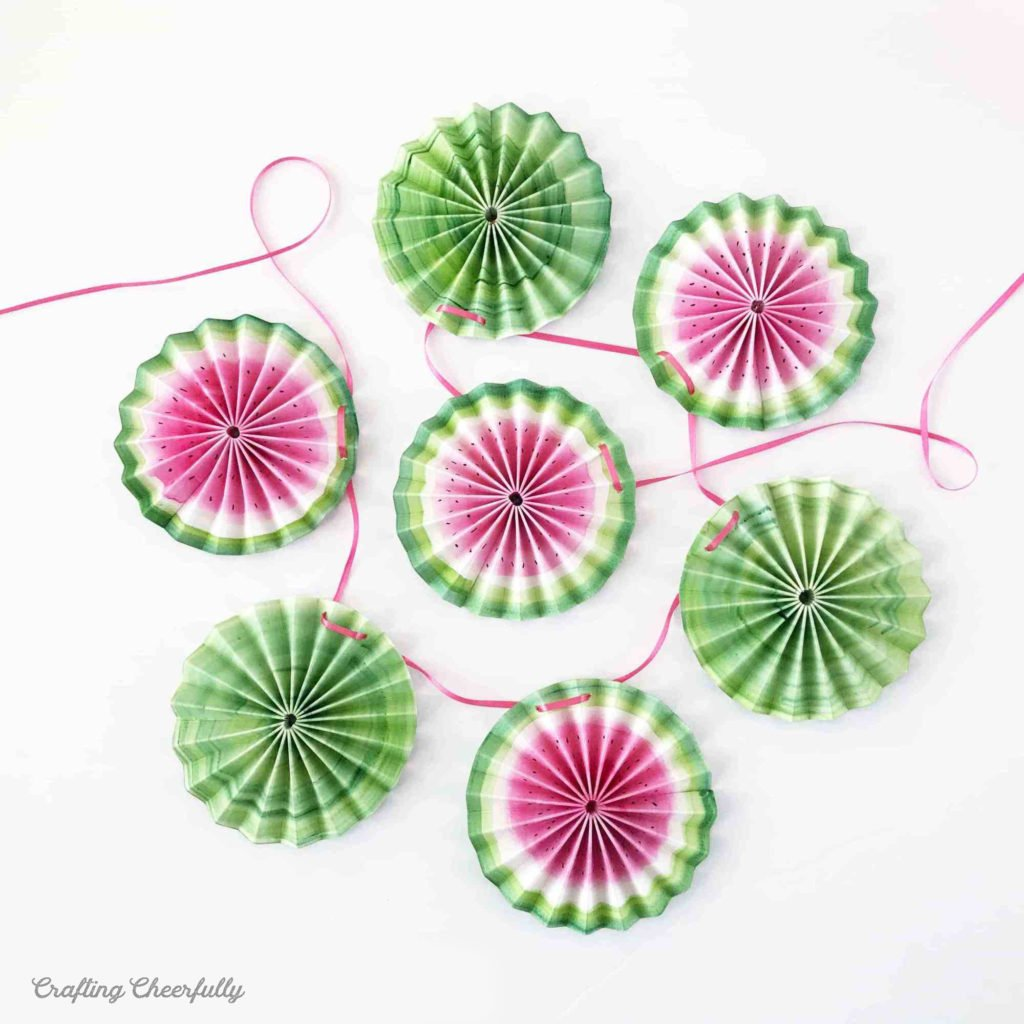 Watermelon Banner made from paper medallions lay on a white table.