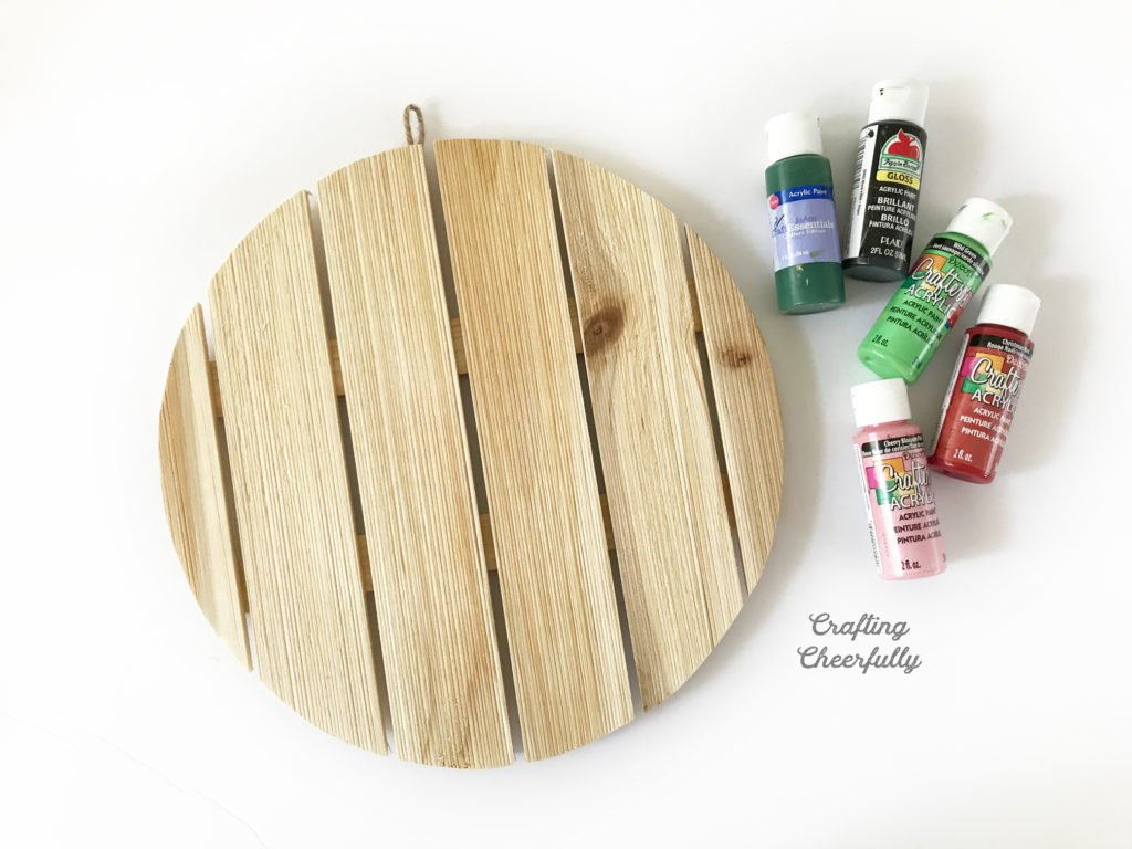 Circular wooden plaque with four bottles of acrylic paint next to it.