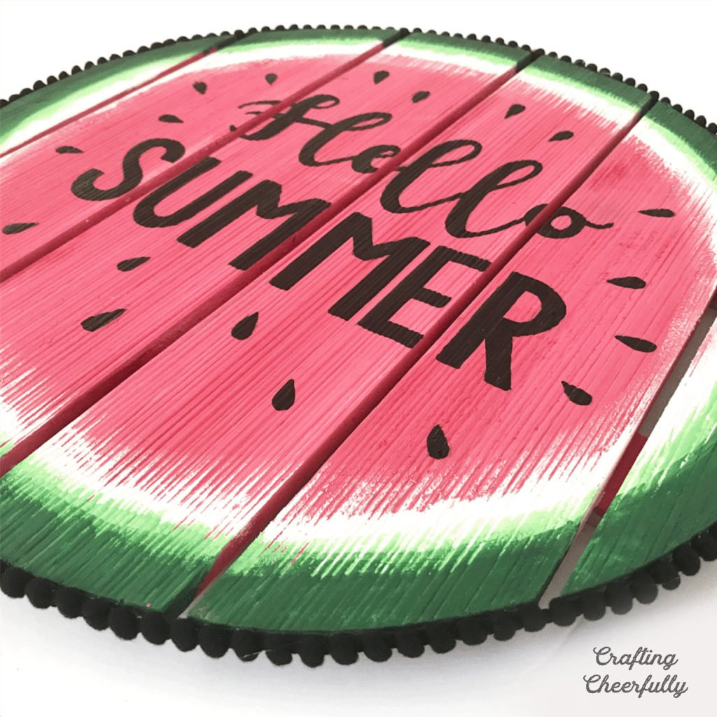 """Close up shot of Circular watermelon wooden sign with the words """"Hello Summer"""" on it."""