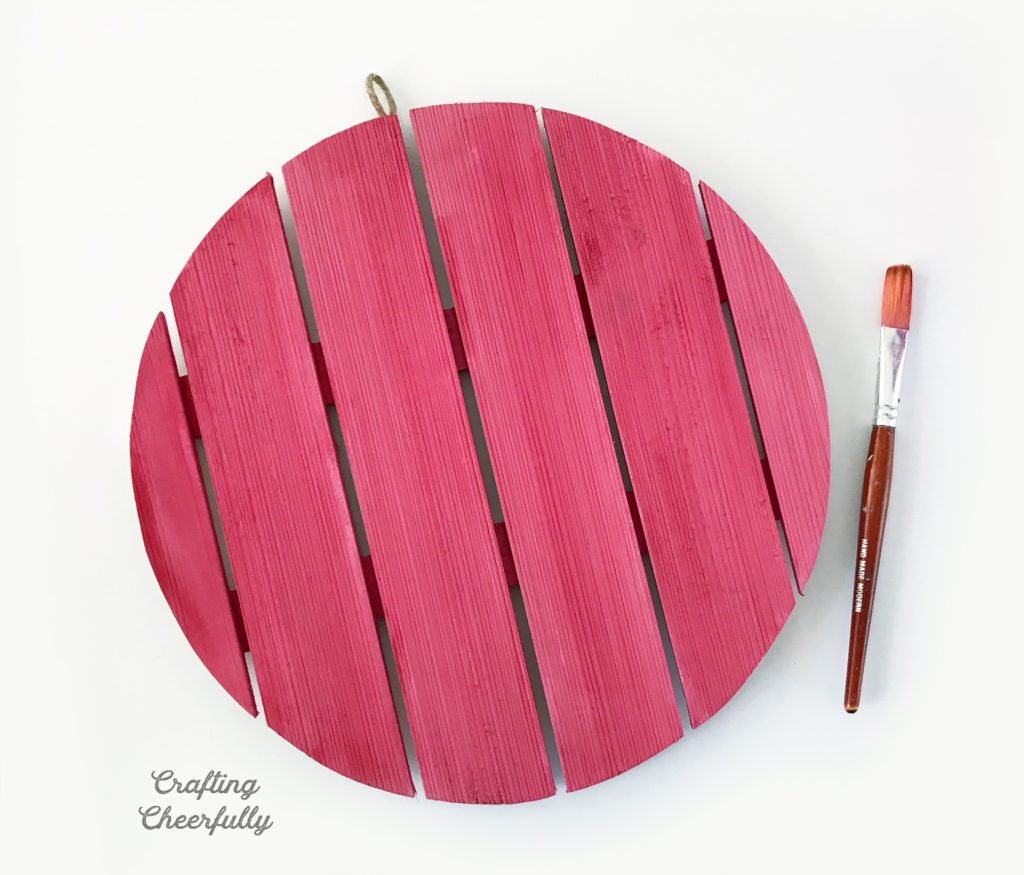 Wooden plaque painted pink. Paintbrush laying next to it.