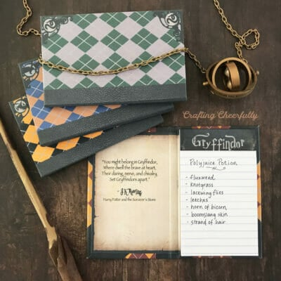 Harry Potter notepads for each Hogwarts house lay on a wooden table next to a time turner and wood wand.