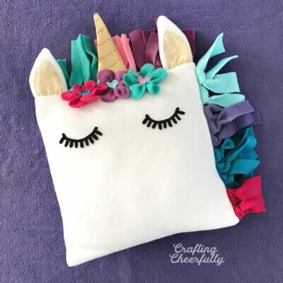 Fleece unicorn pillow with colorful mane and black eyelashes on a purple blanket.