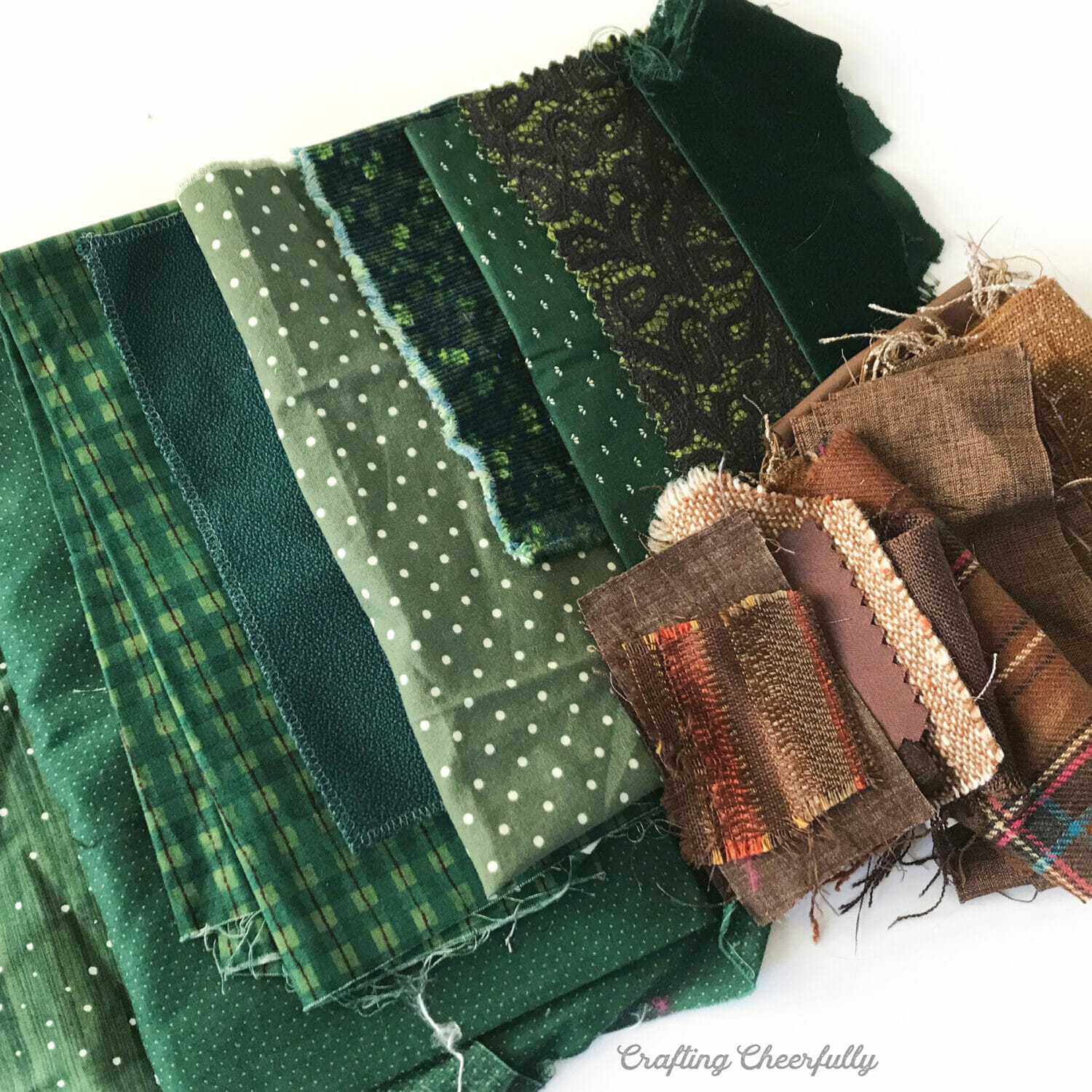 Scraps of green and brown wool used to make the tree banner are arranged on a white table.