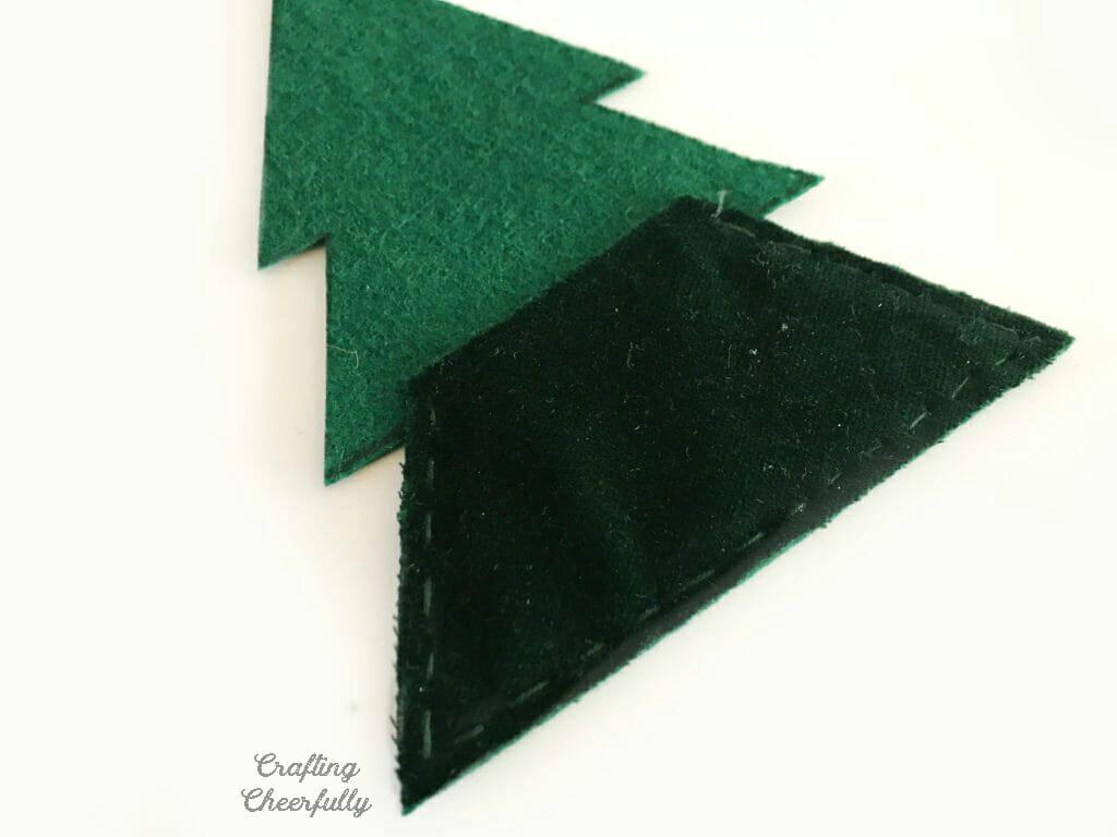 Green felt Christmas tree pennant lays on a white table.
