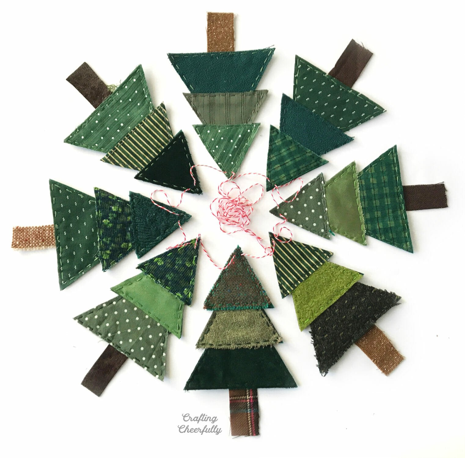Christmas tree banner made with fabric scraps and felt is arranged in a circle with the trees pointing inward.