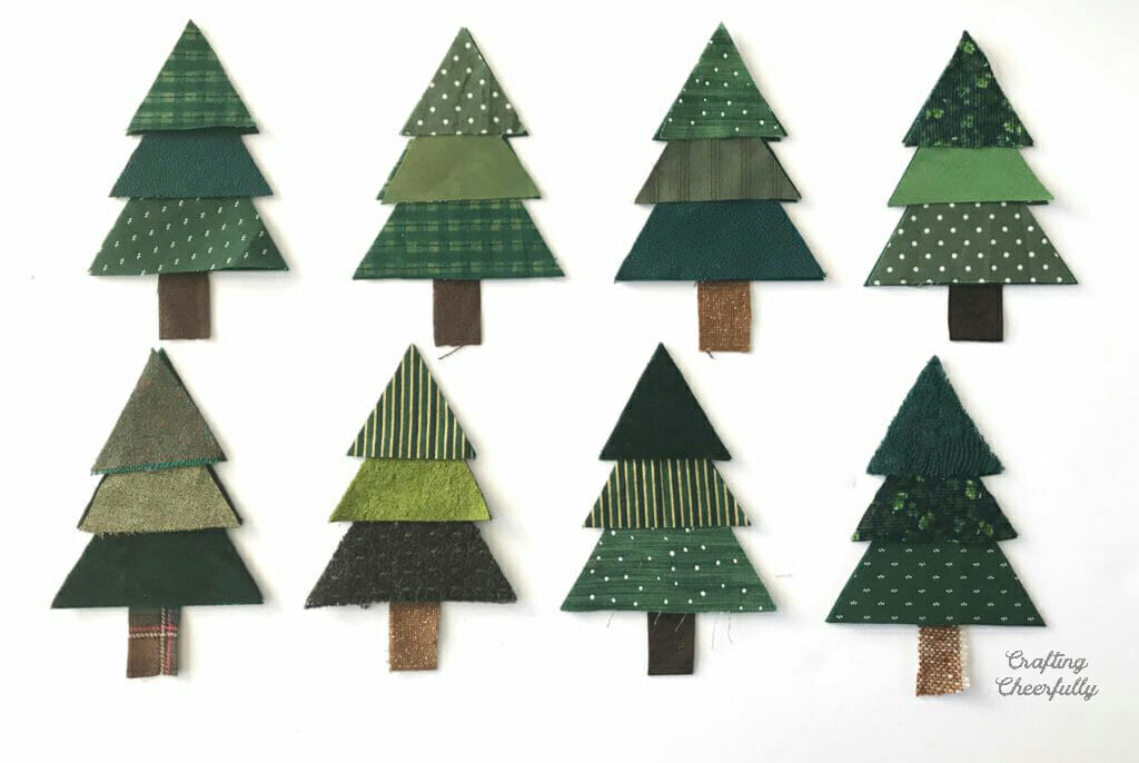 Eight Christmas tree pennants lay on a white table.