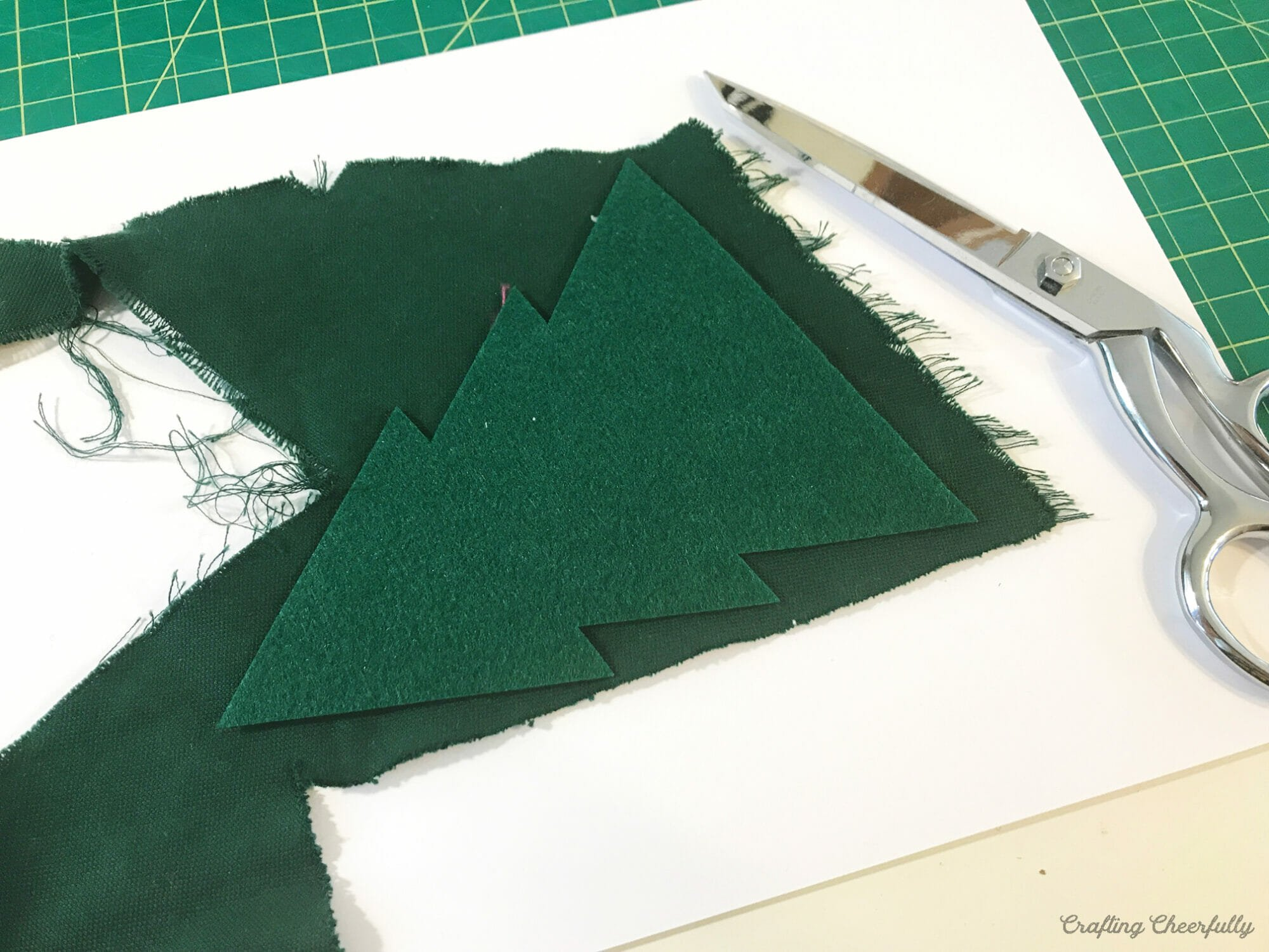 Felt Christmas tree is laid out on a scrap of green wood as a templte.