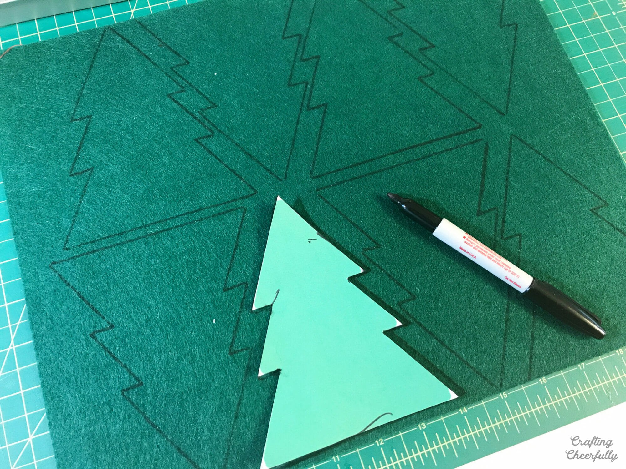 A paper tree template is used to cut Christmas trees from green felt.