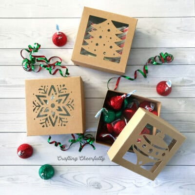 Square boxes with cutout holiday designs filled with red and green candies.