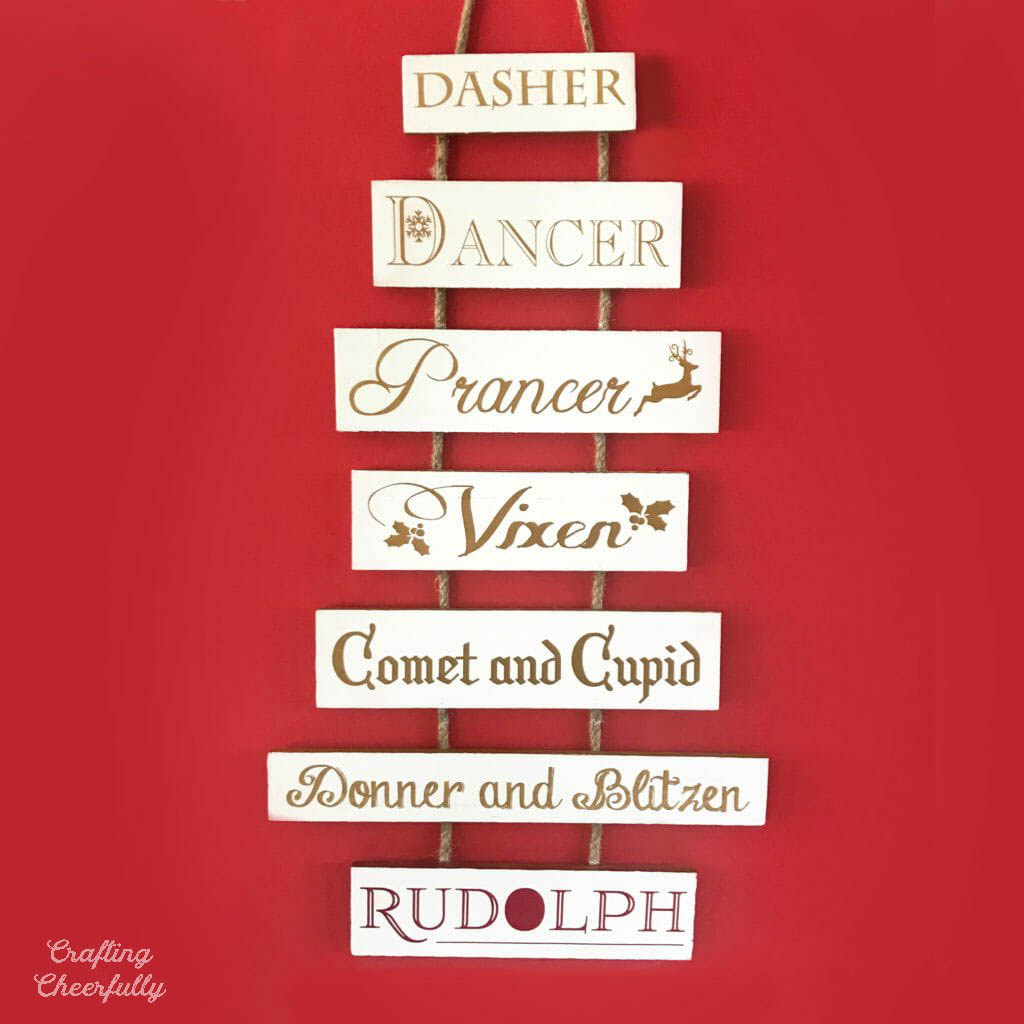 Christmas wooden sign with names of the reindeers listed in different fonts and red foil.