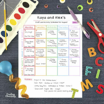 Printable activity calendar on a blue surface surrounded by children's paint, scissors, and magnet letters.