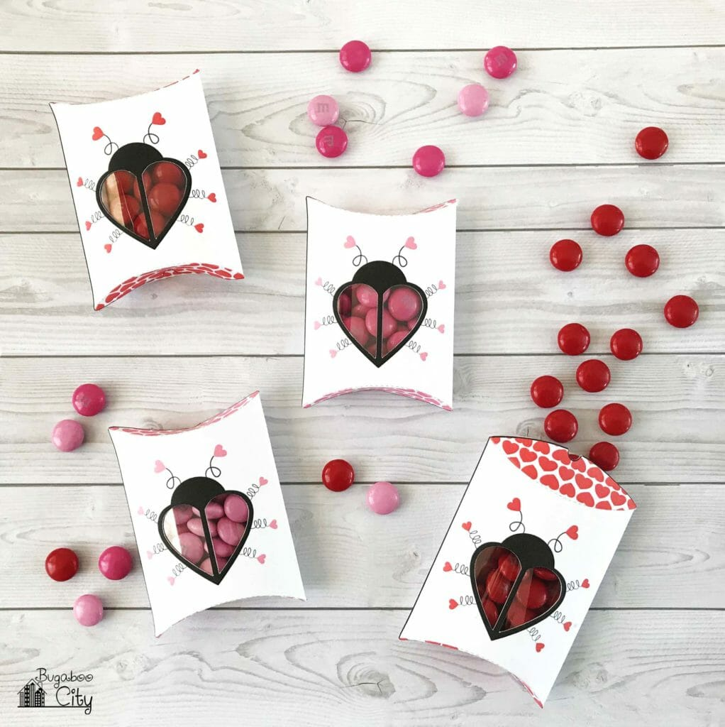 Paper pillow boxes with love bugs on them lay on a wooden table with pink and red m&m's.