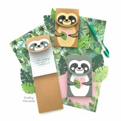 Three cute sloth notepads sitting on tropical themed paper.