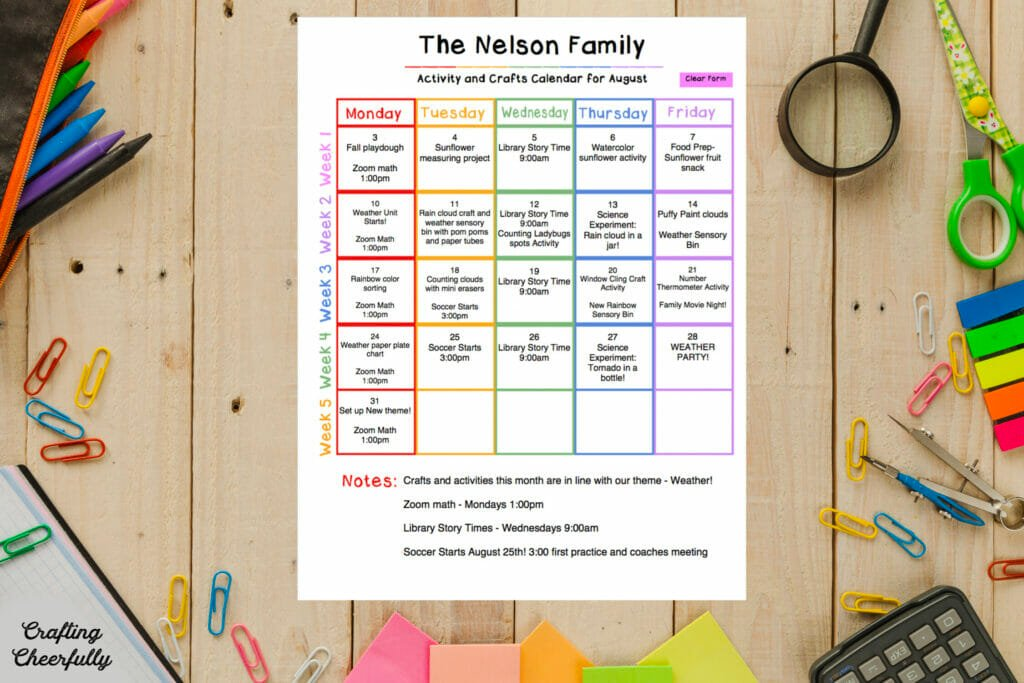 Printable children's activity calendar lays on a wooden table surroundd by colored pencils and desk supplies.