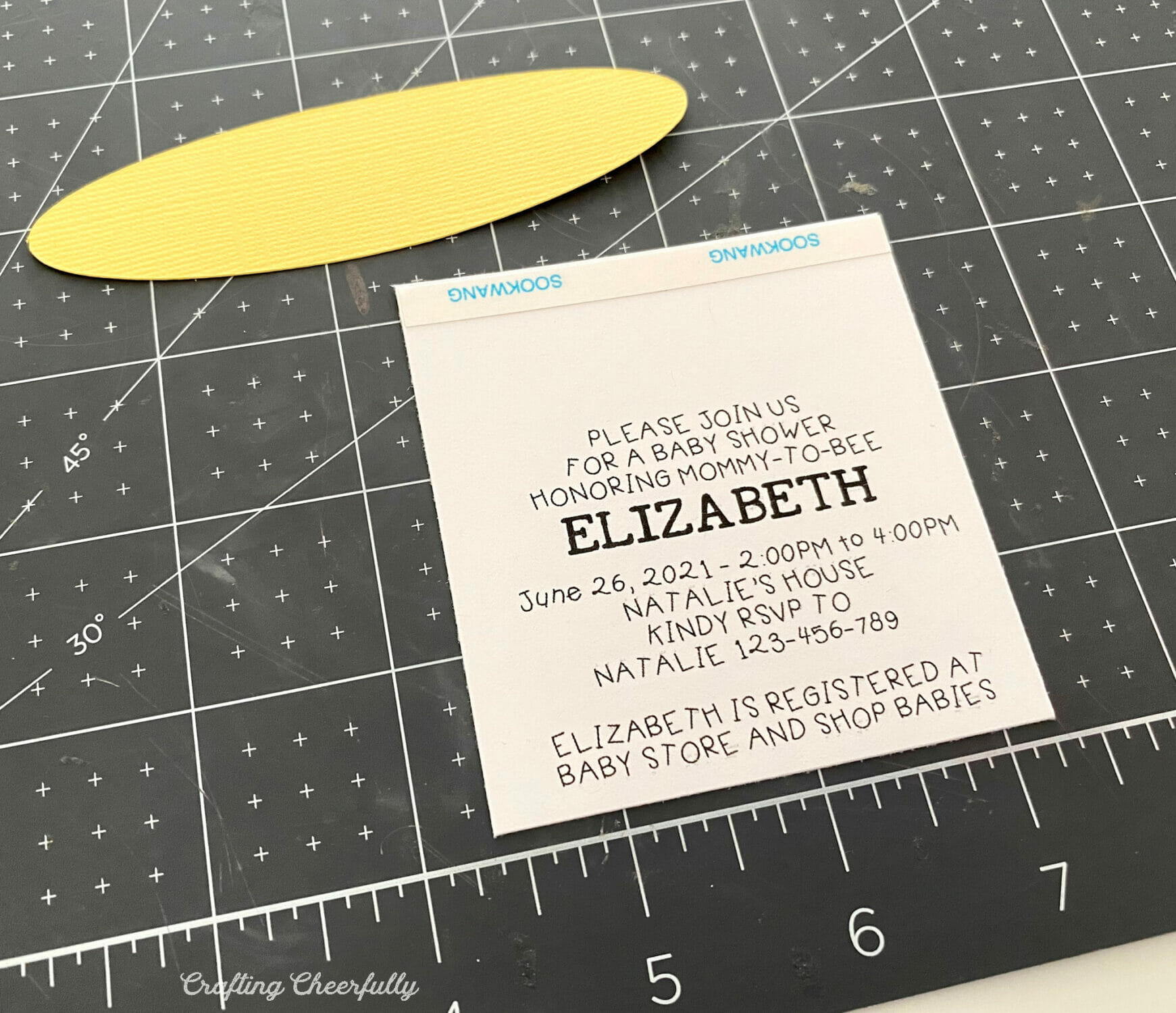 Insert with invitation wording on it lays on a black mat.