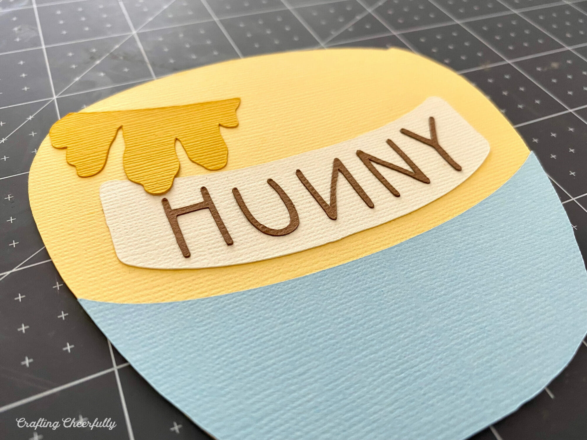 """The honey, and word """"hunny"""" are added to the paper honey pot card."""