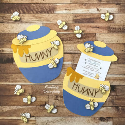 Two blue and yellow honey pot slider cards laying on top of a wooden table.