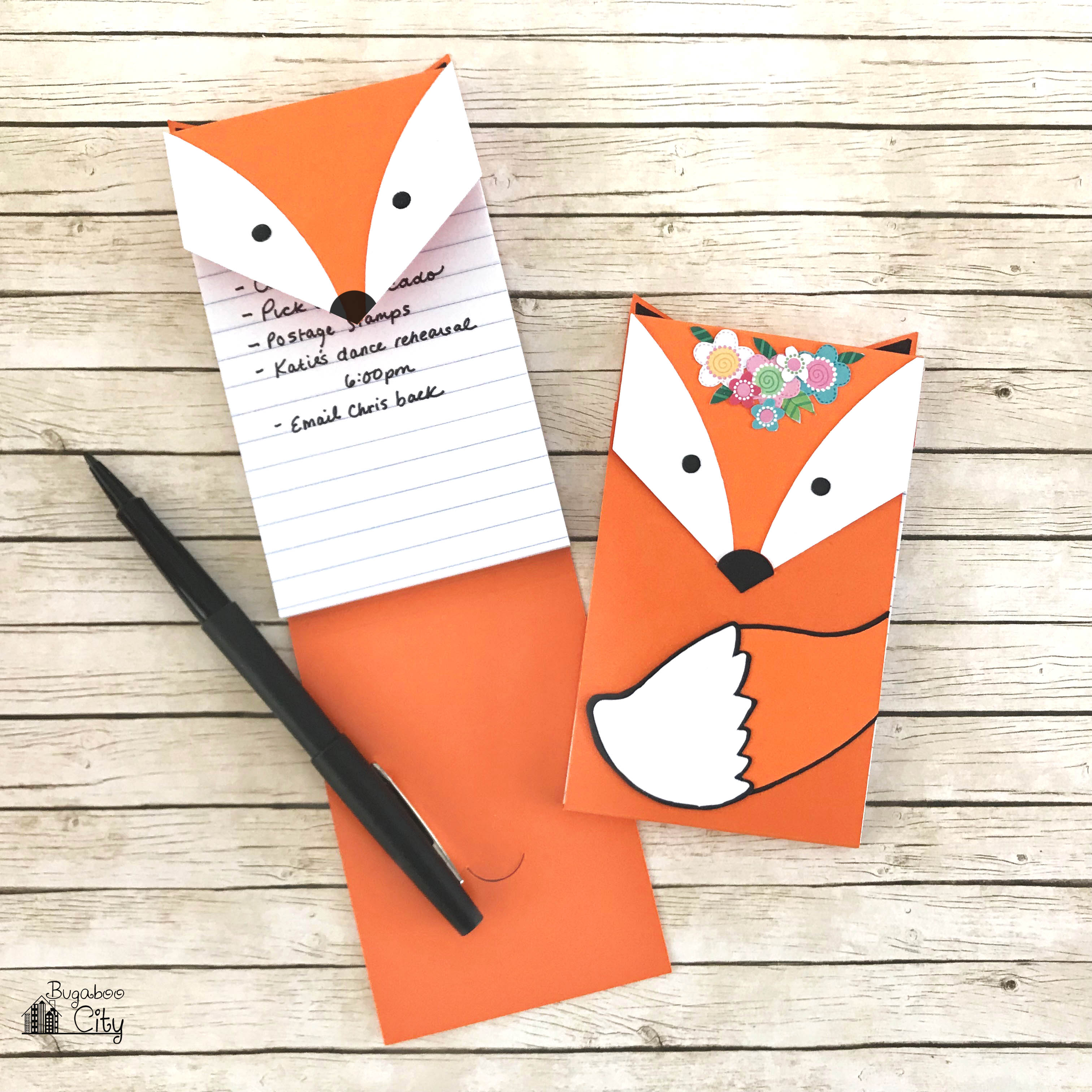 Sweet fox notepads laying on a wooden table with a black pen.