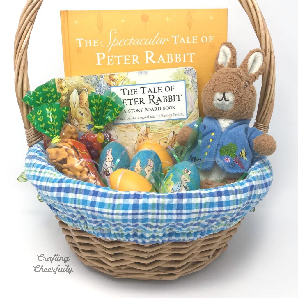 Handmade blue plaid Easter basket liner in a brown basket filled with Easter goodies.