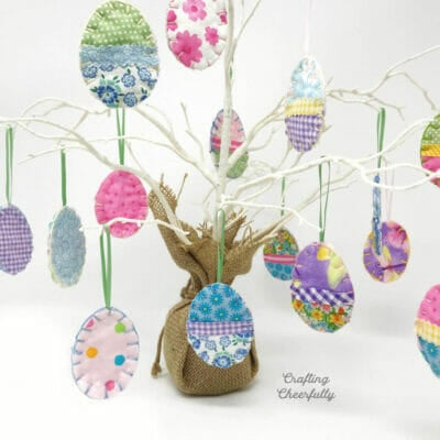 Fabric scrap Easter egg ornaments hang on a white branch tree.