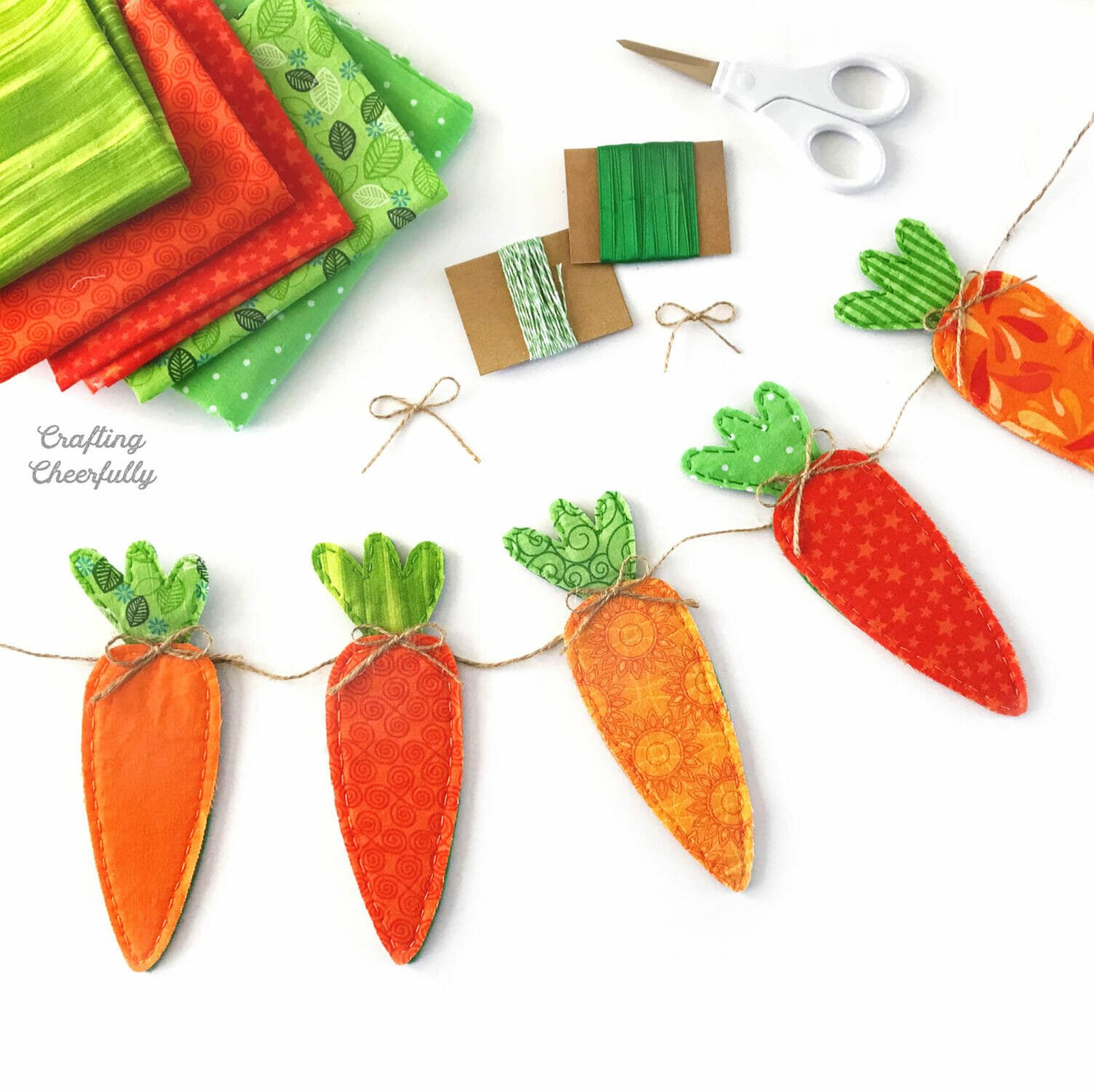 Carrot banner made from fabric scraps on a white table with fabric and ribbon.