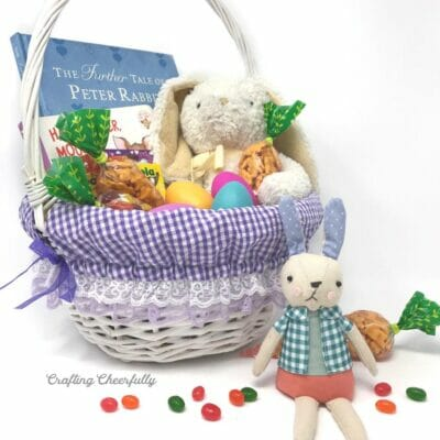 Purple gingham Easter basket liner in a white basket filled with Easter goodies.