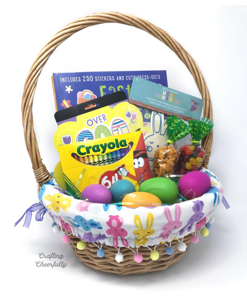 Bunny fabric Easter basket liner with pom poms in a brown basket filled with Easter goodies.