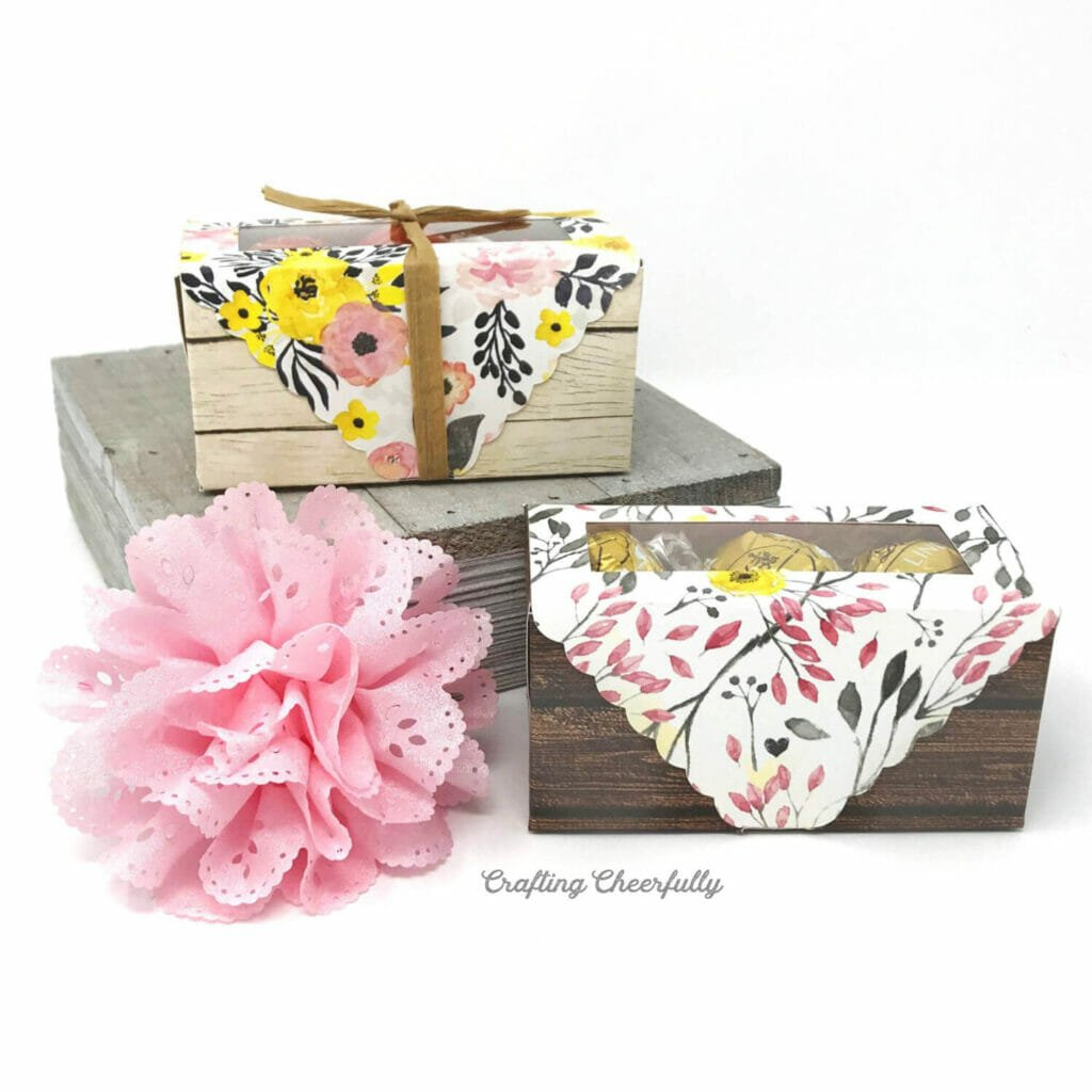 Two rectangle candy boxes made from floral and wood scrapbook paper sit next to a pink flower.