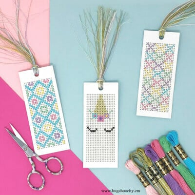 Three unicorn-themed bookmarks laying on a colorful background with embroidery floss and a scissors.
