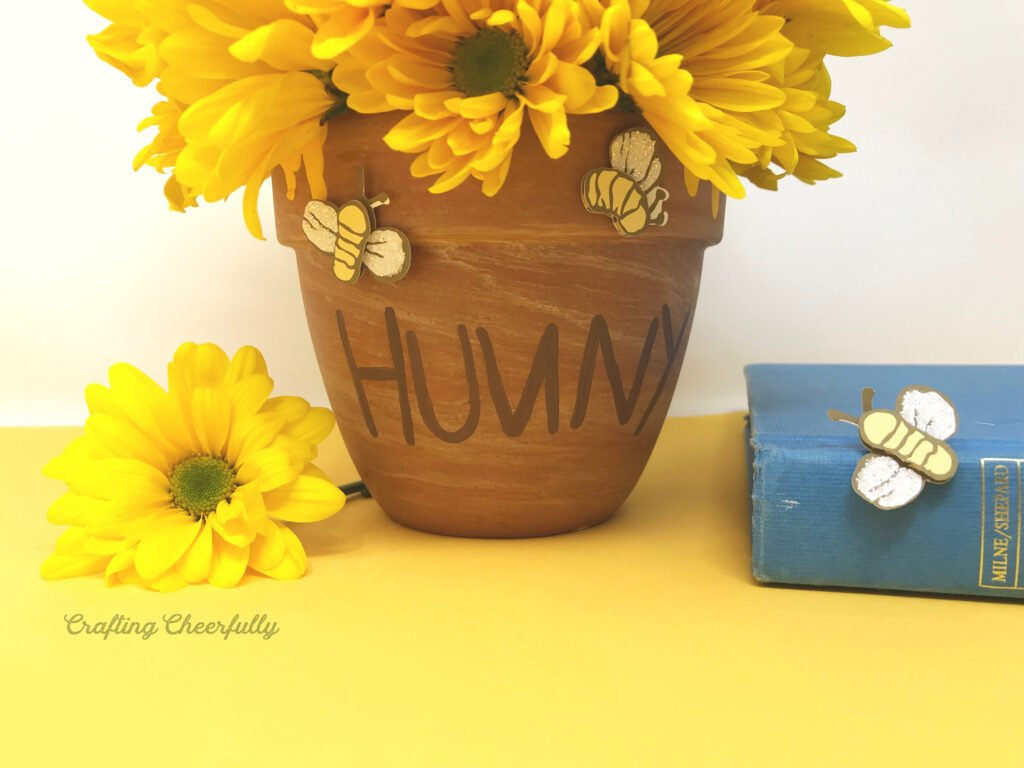 Terra cotta honey pot with yellow flowers on a yellow table next to a classic Pooh book.