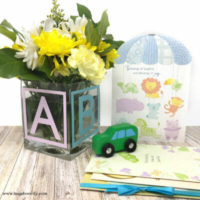 Vase made to look like a baby block with the letters ABC on it sits next to a baby shower cards and a toy car.