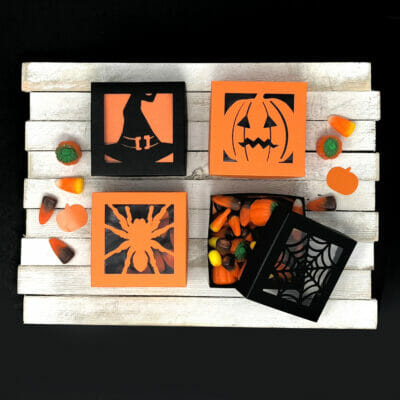 Black and orange boxes with Halloween cut out designs filled with candy corn and sweets.