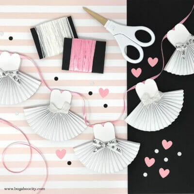 White wedding dress banner made from paper lays on pink striped paper with white and pink ribbon.