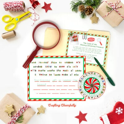 Printable decoder wheel activity lays on a table next to a red magnifying glass and Christmas accessories.