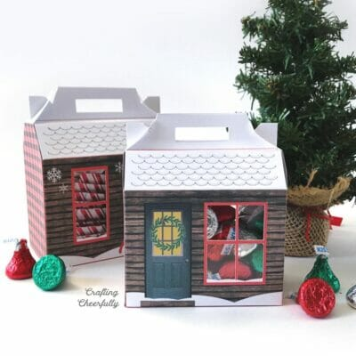 Two paper treat boxes that look like holiday cabins sit next to chocolate candies and a tiny pine tree.