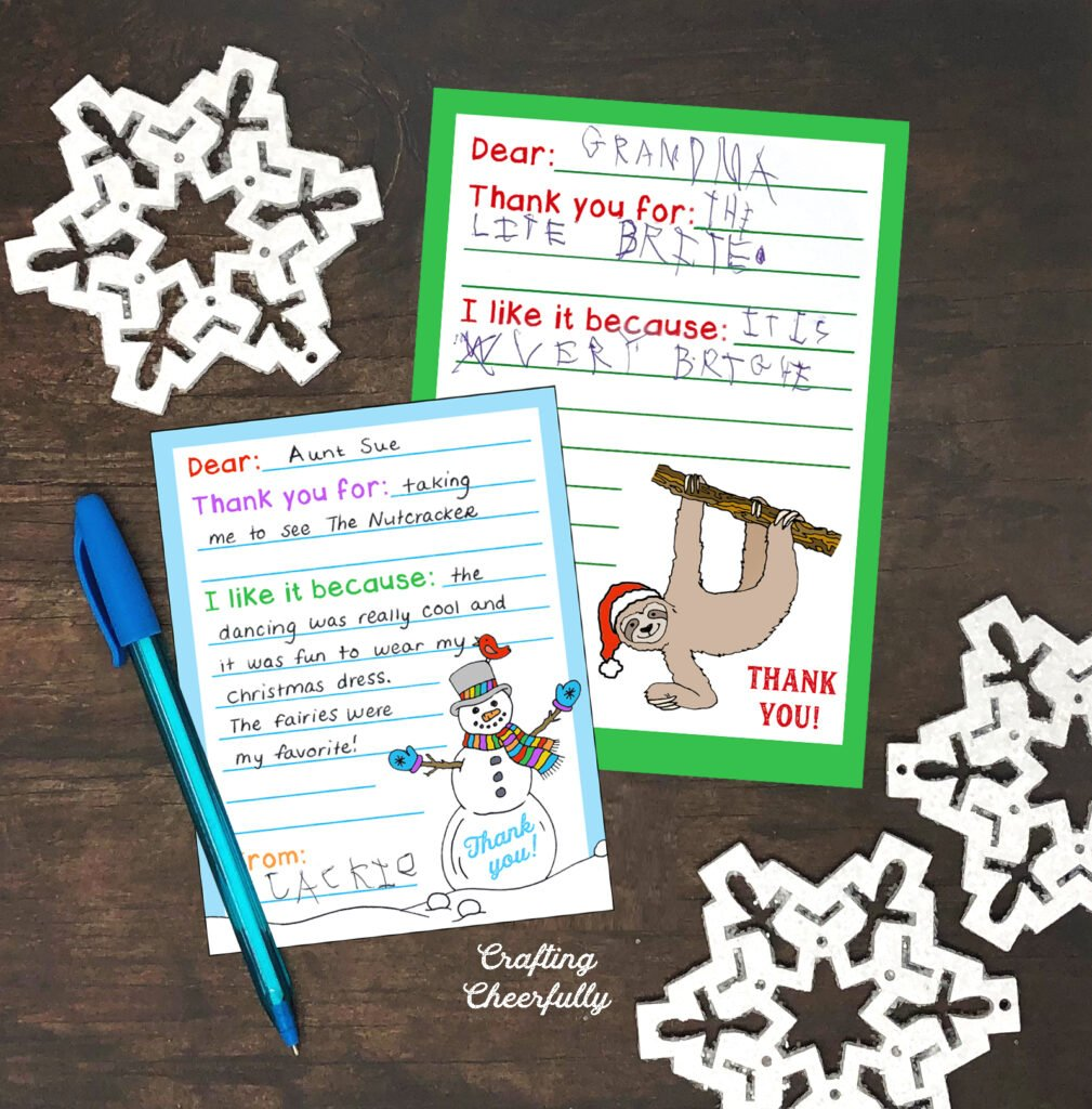 The two printable thank you cards lay on wood table with white wooden snowflakes laying next to them. The thank you cards are filled out by kids.