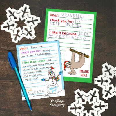 Holiday thank you cards lay on a wooden table with white snowflakes.