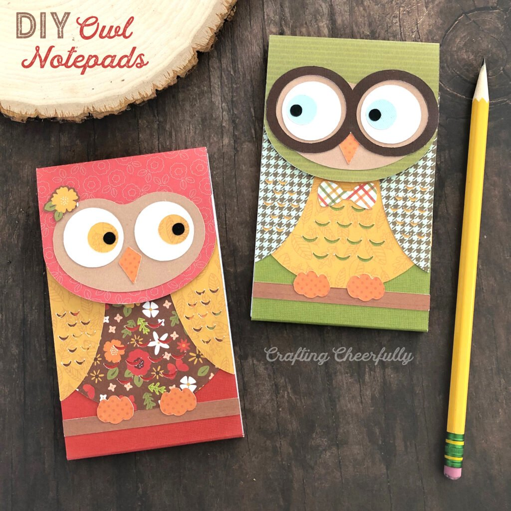 Owl notepads in autumn colored paper and prints laying next to a wood slice.