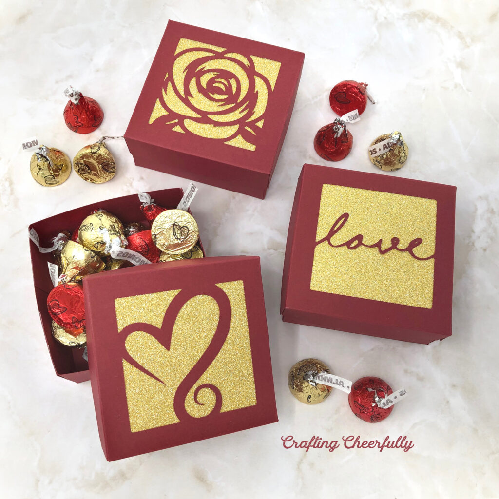 Square boxes made from red and gold paper sit on a marble table. Filled with red and gold candy.