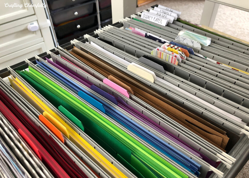 Scrapbook paper in file folders organized by color and pattern.