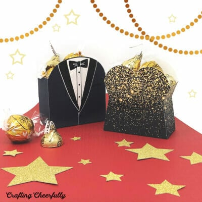 Tuxedo and glamorous gown treat boxes sit on a red carpet with stars.