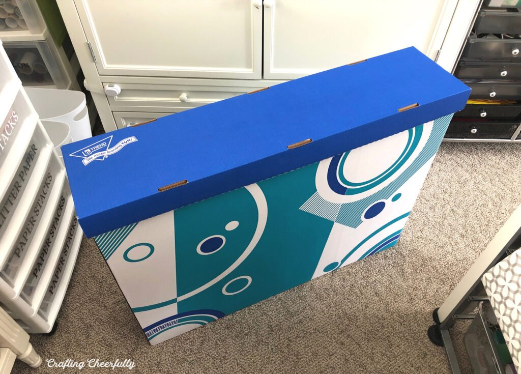 Large poster board is stored in a cardboard box.